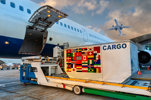 Loading the container with a Many countrie flags in the cargo airplane.