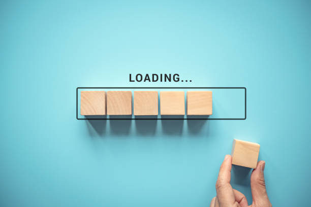 Loading with hand putting wood cube in progress bar. stock photo
