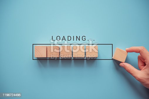 istock Loading with hand putting wood cube in progress bar. 1196724495