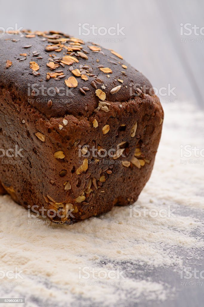 loaf of black bread with flour on the table stock photo