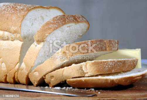 Crusty loaf of finest bread on a bread board with a platter of butter in the background and the knife that sliced it in the foreground. Good sharpness through the image.