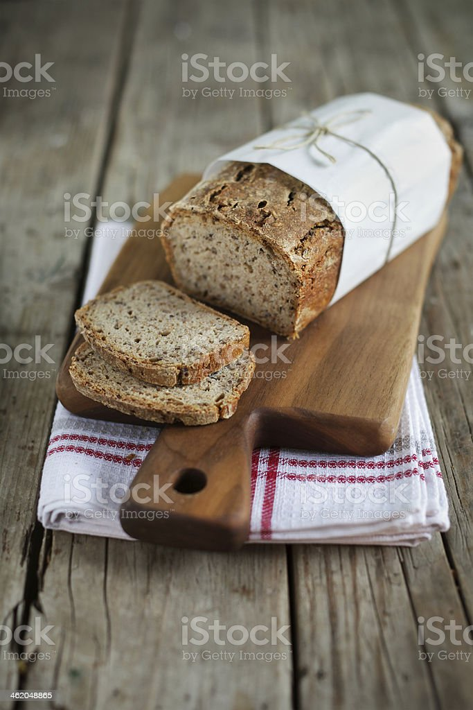 Loaf of oat bread on a wood cutting board stock photo