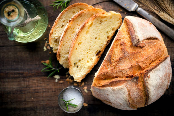 Loaf of rustic homemade bread Rustic loaf of homemade bread served with olive oil, rosemary and salt on dark wooden table. Overhead view bread stock pictures, royalty-free photos & images