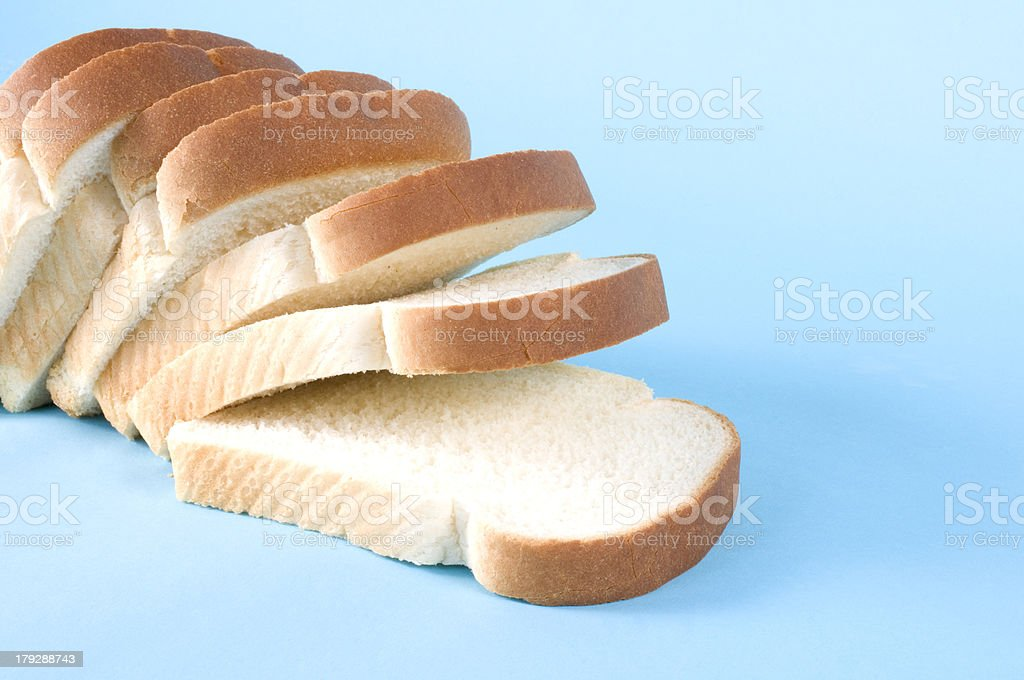 Loaf of sliced white bread on blue background stock photo