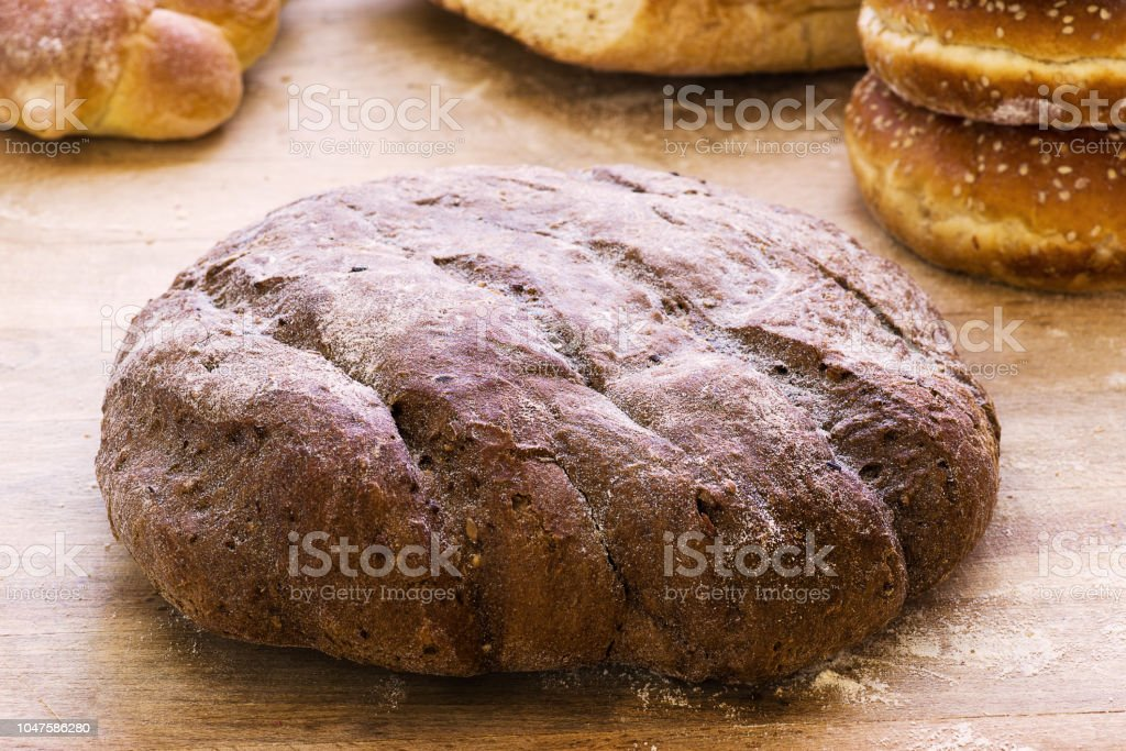 Loaf of wholemeal bread on wooden background. - foto stock