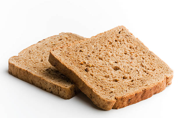 loafs of bread two brown bread loafs on white background whole wheat stock pictures, royalty-free photos & images