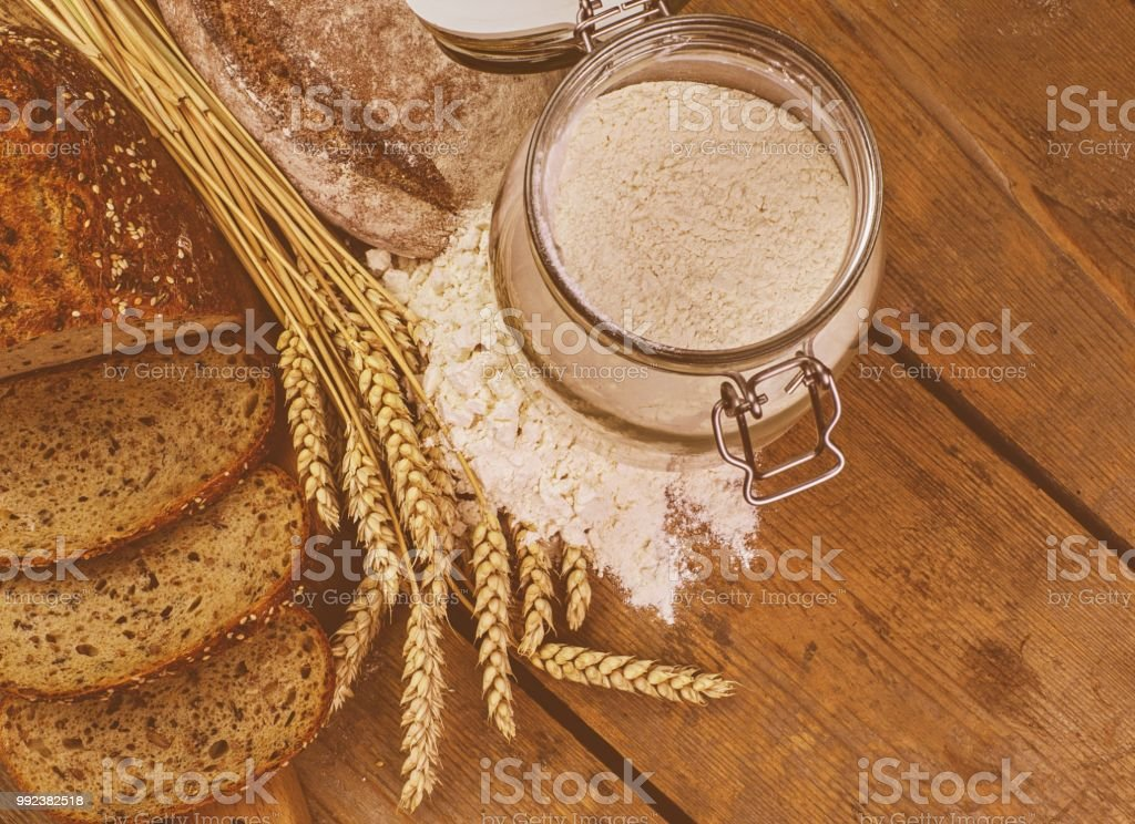 Loafs of bread, slices of bread, wheat flour and ears of grain on wood background. Rustic and rural concept. Close up. Flat lay stock photo
