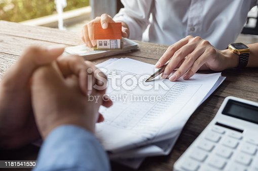 istock Loan agreement, real estate agent or bank officer describes the loan interest to the customer, along with loan documents with a home-style pen and a replica money on a wooden table. 1181541530