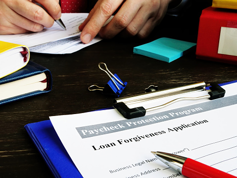 PPP Loan forgiveness application for Paycheck Protection Program in the office.