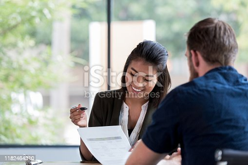 Cheerful young female bank loan officer smiles as she reviews a loan application with a male customer.
