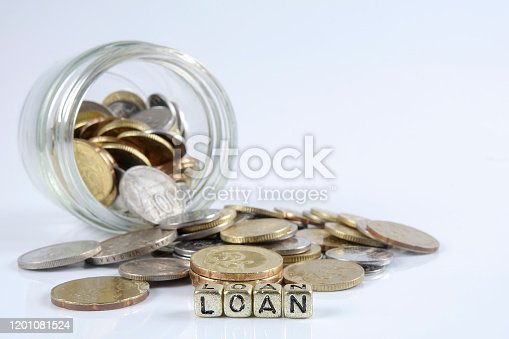 Loan word on a pile on gold coins over white background.