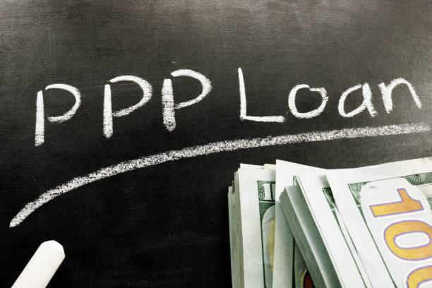 PPP-Darlehen auf der Tafel und Stapel von Bargeld aus Paycheck Protection Program geschrieben. – Foto
