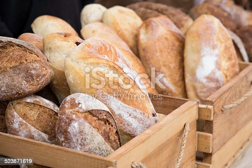 Loaves of homemade bread in wooden crates at an outdoor farmer's market.