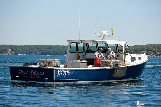 Lobster boat and two lobstermen stock photo