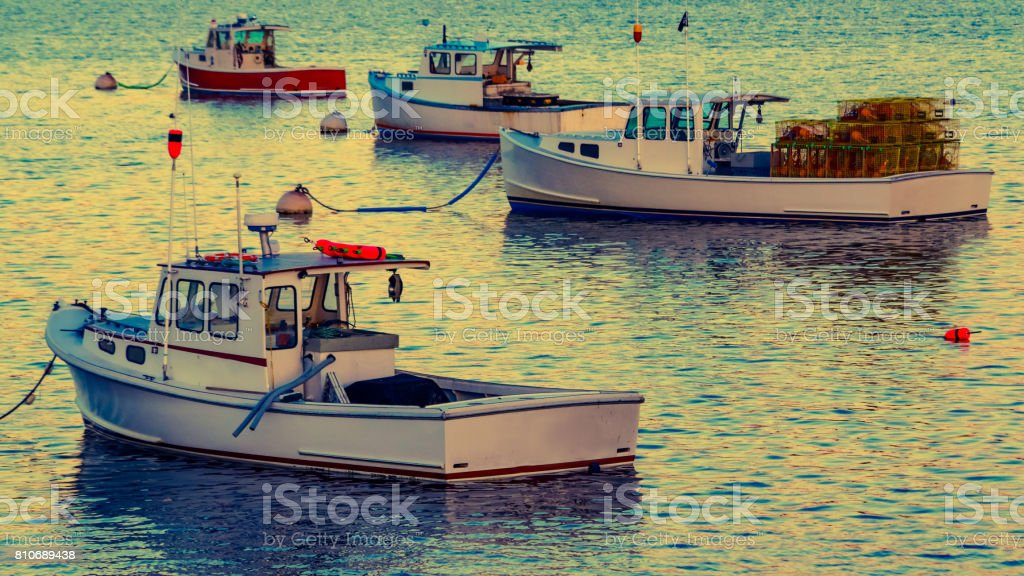 Lobster boats moored in the Sheepscot River at the Wiscasset Waterfront at sunset stock photo