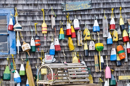 An array of colorful lobster Lobster Bouys on a old shack on Cape Cod are offered for sale.