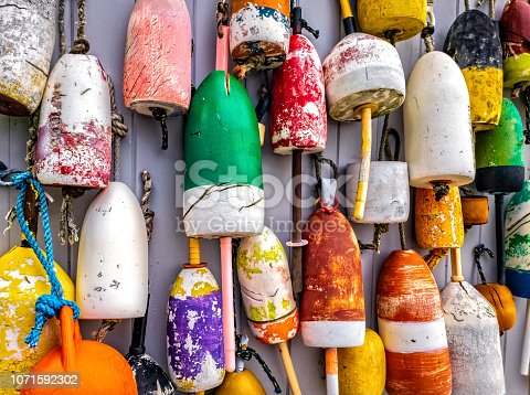 Colorful lobster buoys hang on the outside wall of a fishing shack, in Maine