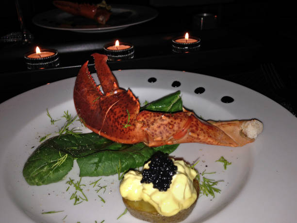Lobster claw with potato, garlic mayonnaise and caviar on a white dinner plate in a romantic setting stock photo