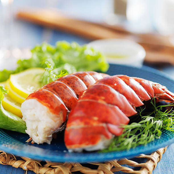 lobster dinner with lemon and lettuce - tail stock photos and pictures