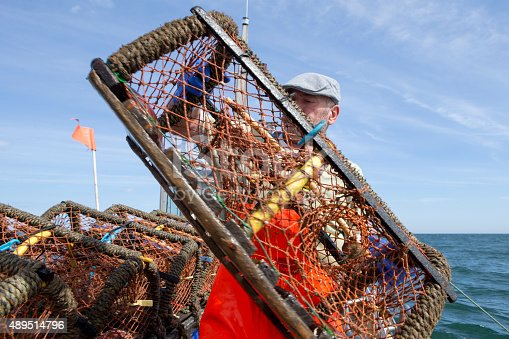 A happy fisherman pulls his lobster pot out of the sea into his boat. He is wearing bright orange overalls and blue gloves to protect his hands.
