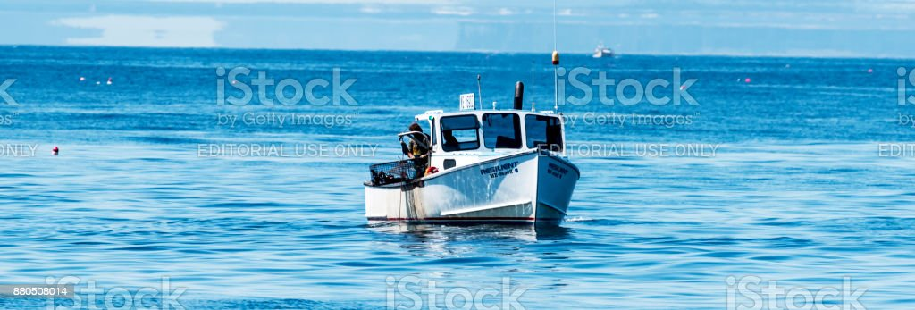 Lobster fishing boat lifting up a lobster trap from the ocean stock photo