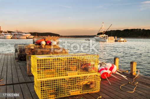Pier in Maine Harbor with lobster traps in foreground and Lobster boats in background.
