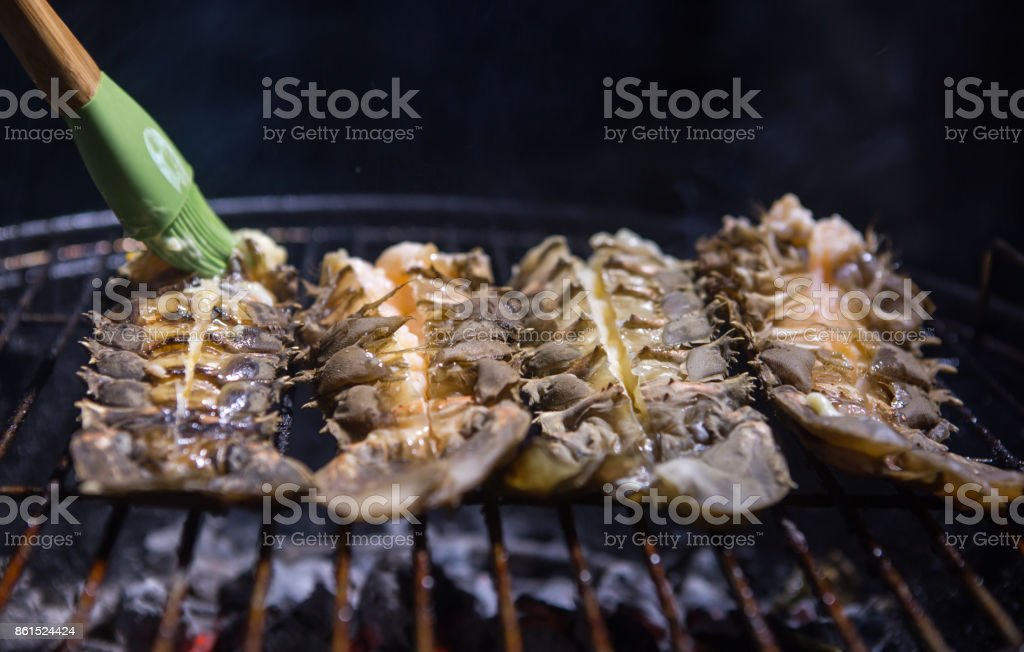 Lobster on the grill. Buttering lobster on grill stock photo