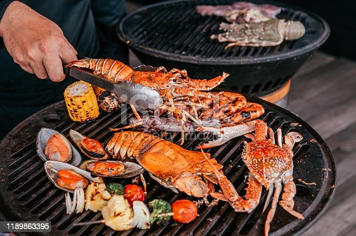 Lobster, rock lobster and mix seafood barbecue cokking on grill - seafood dinner party concept