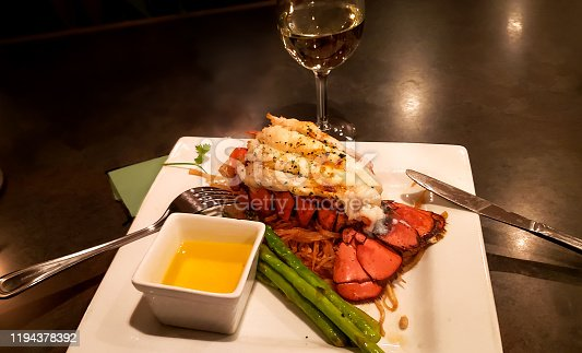 Platter with lobster tail, asparagus and melted butter; glass of white wine in background