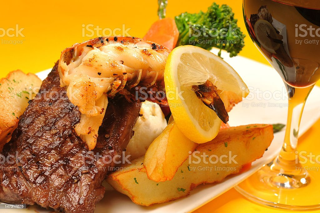 Lobster tail on a new york steak with red wine stock photo