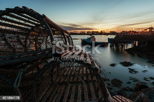 Wooden lobster traps are stacked on the wharf of a Nova Scotian fishing village in dusk light.  Long exposure.