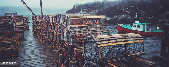 A fishing village wharf is lined with lobster traps during an ice storm.