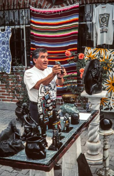 mexiko-stadt, mexiko - 12. august 1998: lokale künstler zeigt aztekische souvenirs aus obsidian hergestellt. obsidian ist ein natürlich geformte vulkanisches glas, das war ein wichtiger bestandteil der materiellen kultur der präkolumbianischen mesoamerika - typisch 90er stock-fotos und bilder
