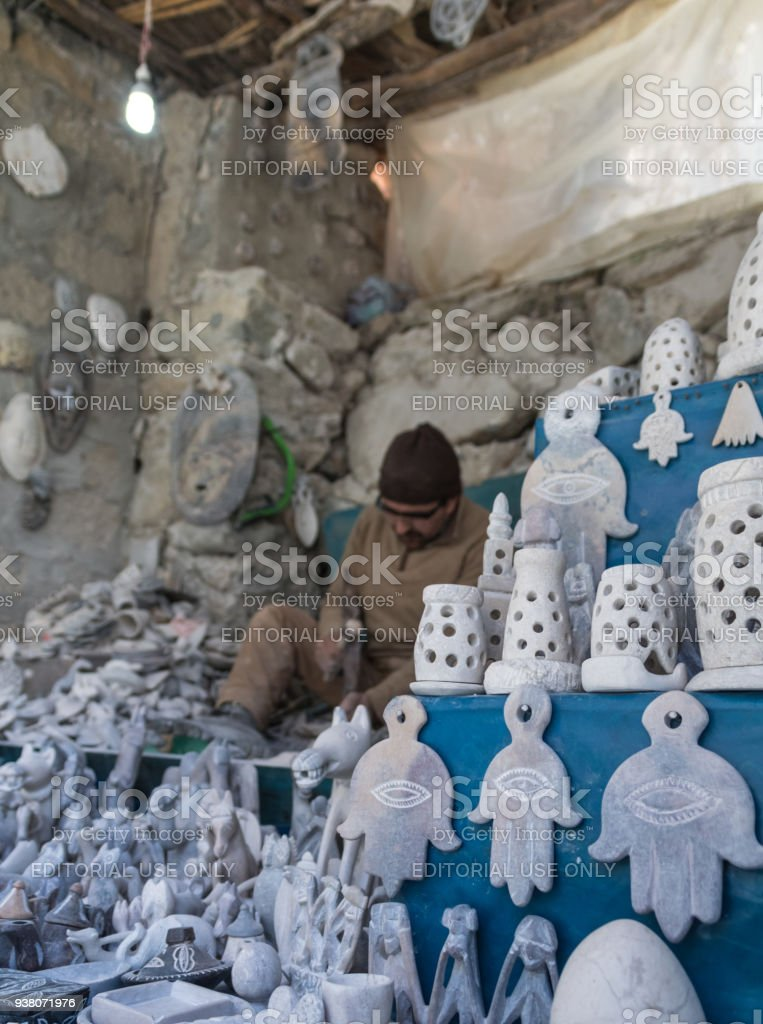 Local Berber man carves Alabaster stone into souvenirs in Ourika Valley, Morocco stock photo