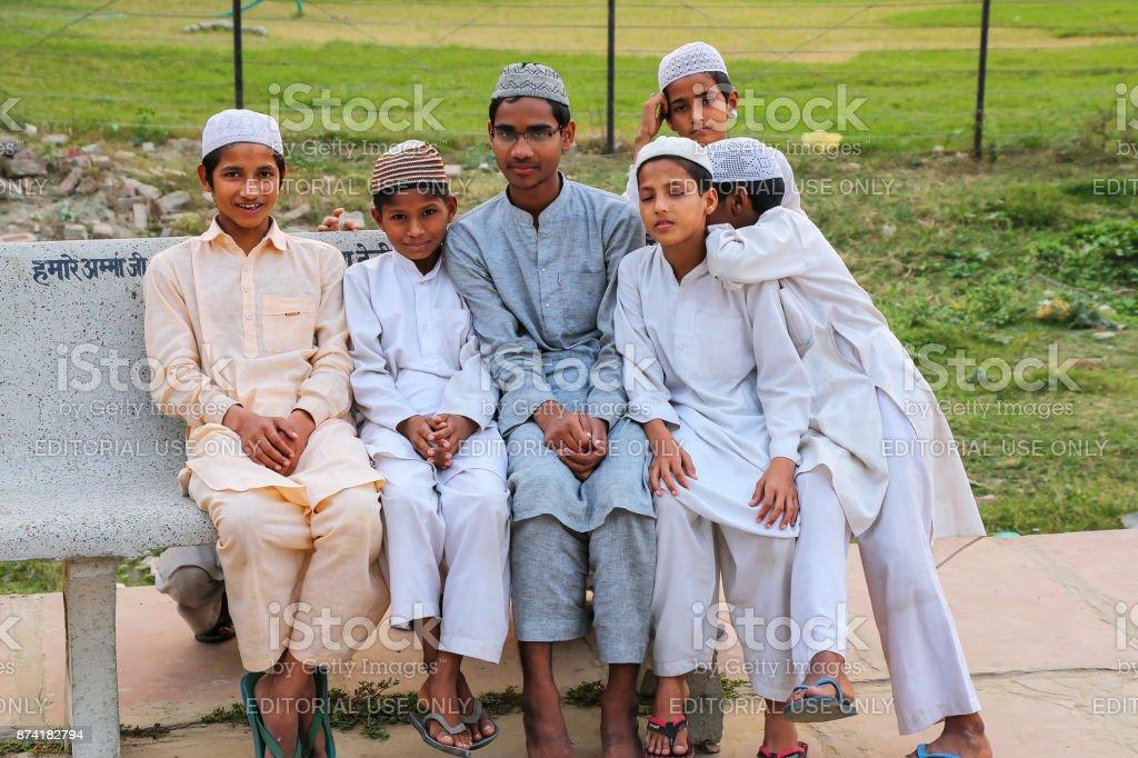 Local boys sitting outside Taj Mahal complex in Agra, India stock photo