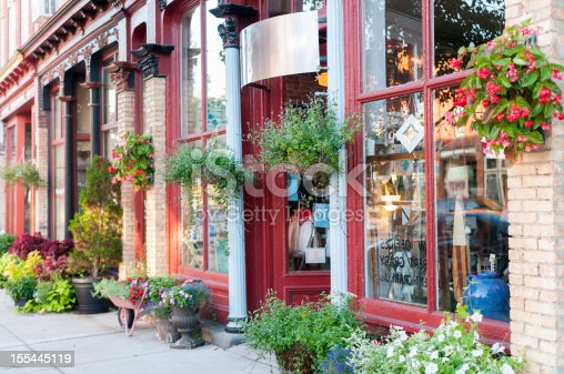 Stretch of local businesses in a historic downtown district. First storefront in focus is an antique shop.