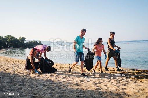 Group of friends collecting trash on beach early in the morning.