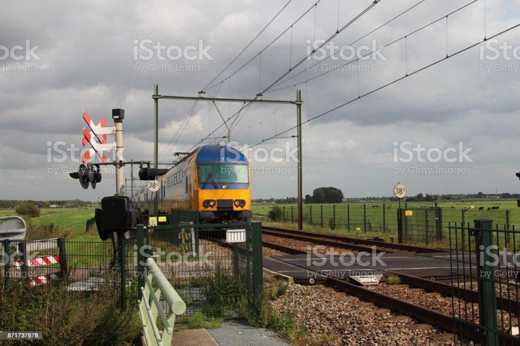 Lokale commuter trein in Moordrecht bij spoorweg kruising foto