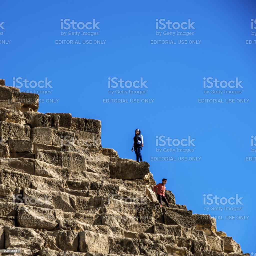 Local egyptians kids playing at the pyramids without caring about heritage. stock photo