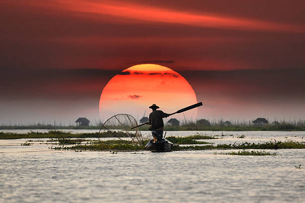 Local fisherman in sunset background The local fisherman in Inle Myanmar myanmar stock pictures, royalty-free photos & images