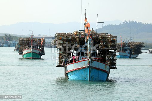 Local fishing boats with fish trap cages on a boat in the river along the coast in Thailand.