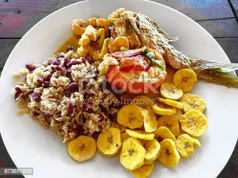 istock Local food. Lobster, red snapper fish, shrimp, rice, beans, fried plantains, coconut milk sauce. Roatan Honduras Creole unique traditional cuisine. Delicious seafood lunch, meal rustic wood background 673657836