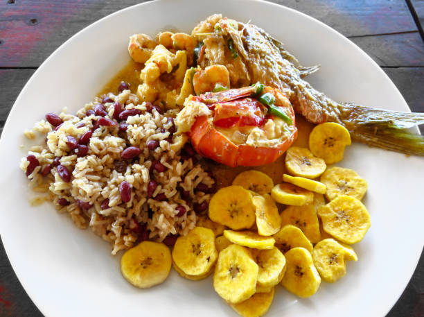 Local food. Lobster, red snapper fish, shrimp, rice, beans, fried plantains, coconut milk sauce. Roatan Honduras Creole unique traditional cuisine. Delicious seafood lunch, meal rustic wood background Lobster, red snapper fish, shrimp, rice, beans, fried plantains, coconut milk sauce. Roatan Honduras Creole unique traditional cuisine roatan stock pictures, royalty-free photos & images