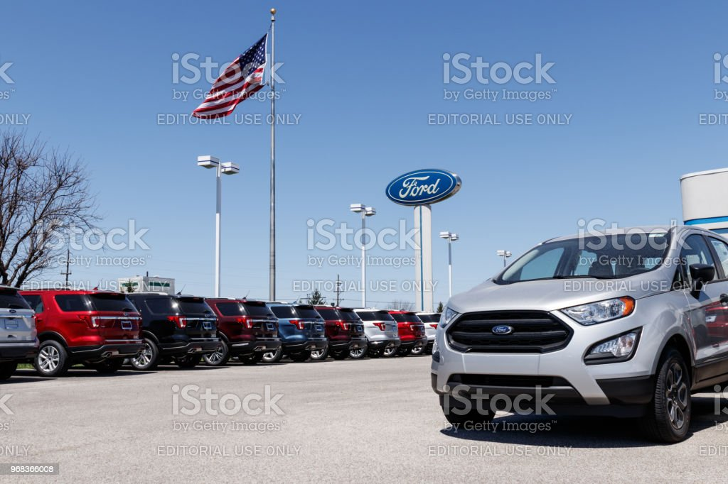 Local Ford Car and Truck Dealership with American flag. Ford sells products under the Lincoln and Motorcraft brands XII stock photo
