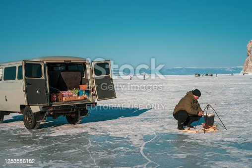 local guide tour prepare table for lunch at the sunny winter day on Lake Baikal. Blue clear ice with cracks in the Small Sea with Car UAZ minibus for tourist.