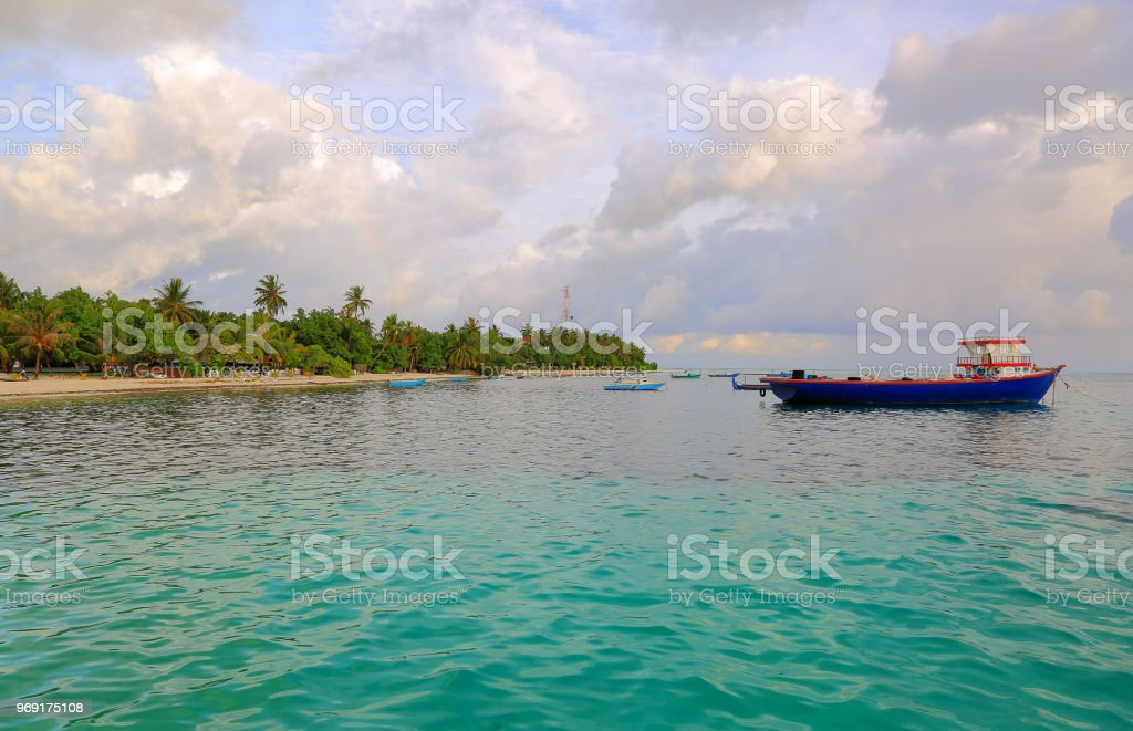 Local harbor in Indian Ocean, Maldives. Dhangethi Island. Small boats on turquoise ocean water on blue sky with white clouds background. stock photo