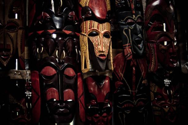 local kenyan handicraft depicting some local masks - kenyan culture stock photos and pictures