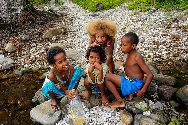local kids playing by the river along lavena coastal walk - fiji stock photos and pictures