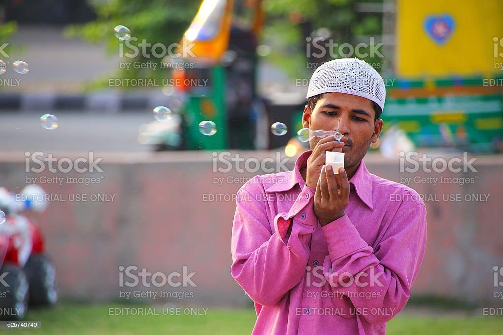 Local man making soap bubbles at Man Sagar Lake waterfront stock photo