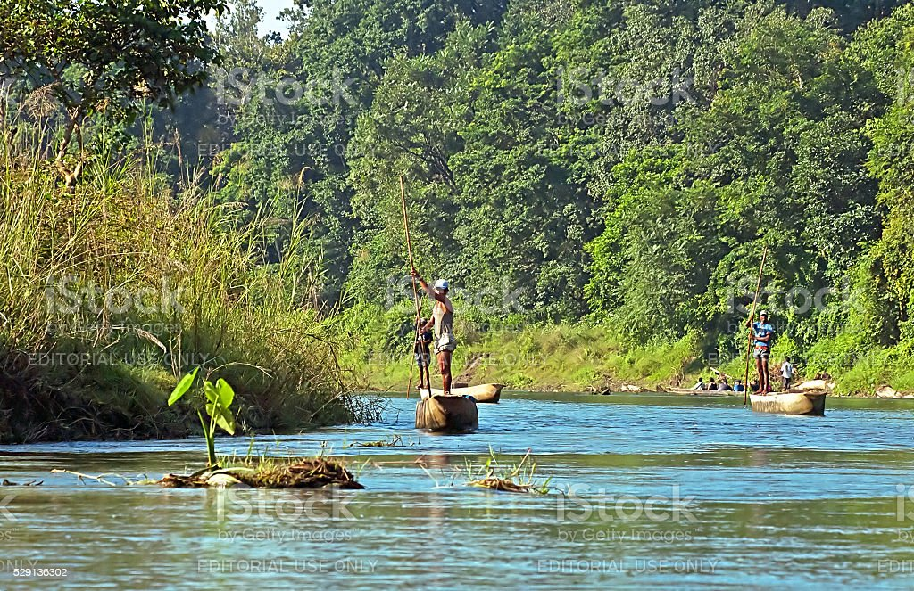Local man traveling by rowboat at wild river stock photo